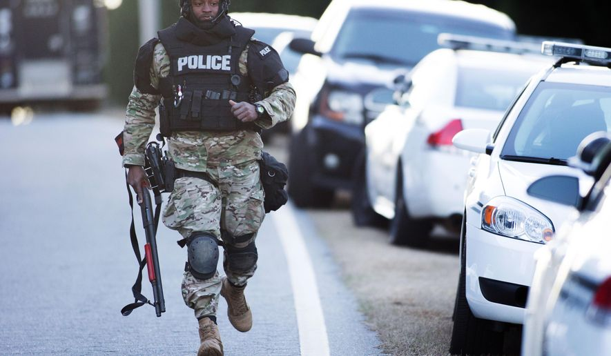 A police officer wearing tactical gear jogs toward the scene of a hostage situation near Beyers Landing Drive, Wednesday, Jan. 6, 2016, in Buford, Ga. The Gwinnett County SWAT team is in a standoff with an armed man who is holding a 2-year-old hostage in a Buford neighborhood. (Branden Camp/Atlanta Journal-Constitution via AP) MARIETTA DAILY OUT; GWINNETT DAILY POST OUT; WXIA OUT; WGCL OUT; FOX 5 OUT; MANDATORY CREDIT