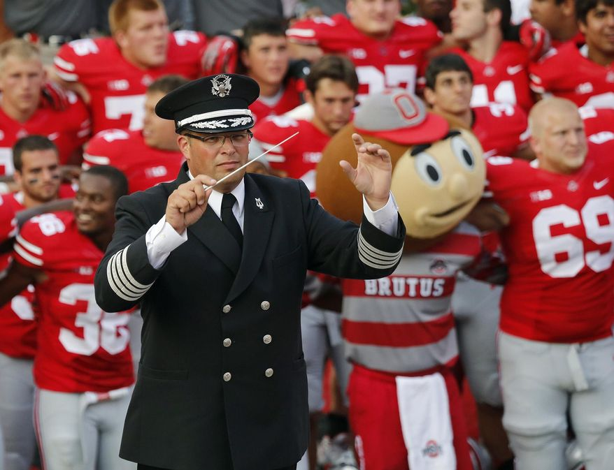 """FILE - In this Sept. 7, 2013 file photo, Ohio State University marching band director Jonathan Waters leads the band in """"Carmen Ohio"""" following a NCAA football game against San Diego State at Ohio Stadium in Columbus, Ohio. Waters, the Ohio State University's fired marching band director, can no longer afford the high-powered legal team that has been helping him fight for reinstatement. In court filings Wednesday, Jan 6, 2015,  members of a team that included a former assistant U.S. attorney and a former Ohio attorney general asked to withdraw as counsel for Waters. (Adam Cairns/The Columbus Dispatch via AP, File)"""