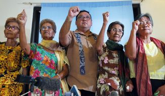 """Four of the remaining 32 alleged WWII sex slaves clench their fists along with their legal counsel Harry Roque, center, to demand compensation and apology from the Japanese Government during a news conference in Manila, Philippines, Wednesday, Jan. 6, 2016. The announcement Wednesday came following a landmark agreement between South Korea and Japan recently of an """"irreversible"""" settlement of a decades-long standoff over Korean women forced into sexual slavery by Japan's WWII military. They are, from left, Avelina Culala, 85, Isabelita Vinuya, 84, Emilia Mangilit, 83, Isabelita Vinuya, 84 and Candelaria Soliman, 85. (AP Photo/Bullit Marquez)"""