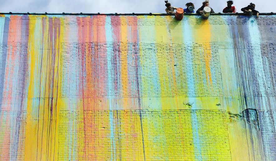 "FILE - In a Sept.25, 2009 file photo, paint is dumped over the side of the building by artists and volunteers to create a massive mural on the side of a vacant building at E.Grand Blvd. near the New Center Area in Detroit,  Mich. Detroit artist Katherine Craig is suing to protect the enormous multicolor mural that's been described as a ""bleeding rainbow"" on a building that could be developed into apartments. Craig fears the mural will be ruined if windows are installed on the building.  (Daniel Mears/The Detroit News via AP)"