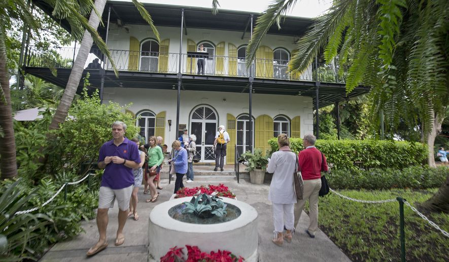 In this Monday, Jan. 4, 2016, photo, provided by the Florida Keys News Bureau, visitors stroll on the entrance path of the Ernest Hemingway Home & Museum in Key West, Fla. A facet of the prize for the winner of the Florida Keys Flash Fiction literary contest is the opportunity to spend up to 10 days writing in the same study that Hemingway utilized when he lived and wrote at the house in the 1930s. (Rob O'Neal/Florida Keys News Bureau via AP)