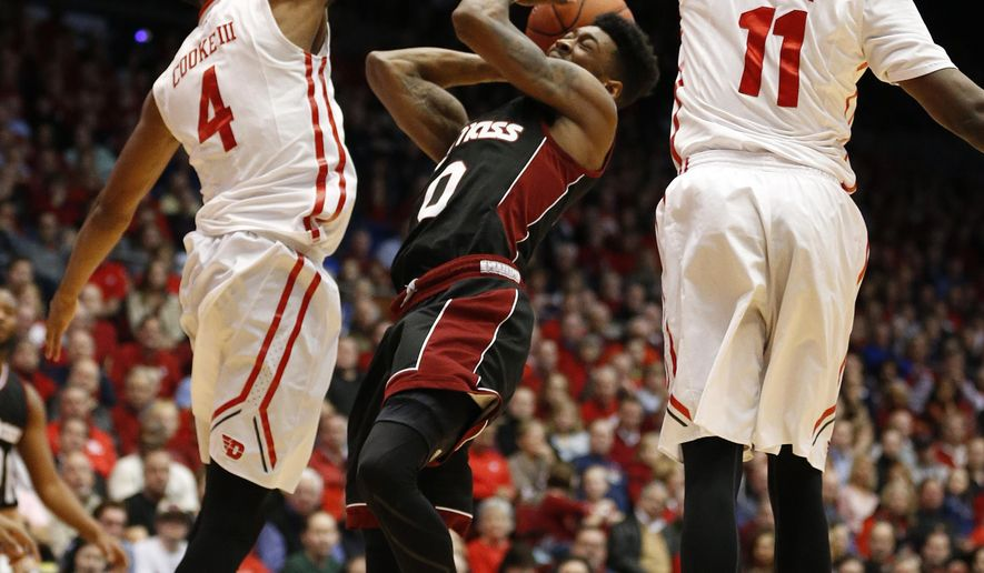 Massachusetts guard Donte Clark (0) attempts a shot between Dayton guard Charles Cooke (4) and Scoochie Smith (11) during the first half of an NCAA college basketball game Wednesday, Jan. 6, 2016, in Dayton, Ohio.  (AP Photo/Gary Landers)