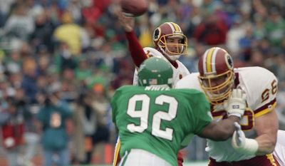 Washington Redskins Mark Rypien passes under pressure from Philadelphia Eagles Reggie White during first quarter action in Wildcard playoff game, Saturday, Jan. 5, 1991 at Philadelphia Veterans Stadium. Holding off White is Redskins Joe Jacoby. Rypien threw two touchdown passes the lead the Redskins to a 20-6 upset win. (AP Photo/Amy Sancetta) **FILE**