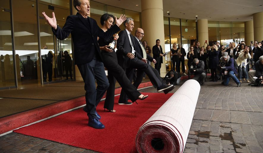 Golden Globes executive producer Barry Adelman, from left, Miss Golden Globe 2016 Corinne Foxx, executive producer Allen Shapiro and Lorenzo Soria, president of the Hollywood Foreign Press Association, roll out the red carpet during the 73rd Annual Golden Globe Awards Preview Day at the Beverly Hilton on Thursday, Jan. 7, 2016, in Beverly Hills, Calif. The annual awards show including film and television will be held on Sunday. (Photo by Chris Pizzello/Invision/AP)