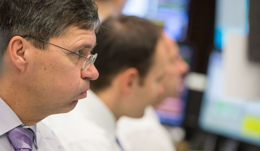 Traders look at their screens at the stock exchange in Frankfurt, Germany, Thursday, Jan. 7, 2016. Germany's DAX stock market index was affected by Chinas stock crisis and dropped below 10,000 points. (Frank Rumpenhorst/dpa via AP)
