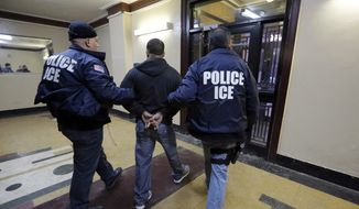 Immigration and Customs Enforcement officers escort an arrestee during a series of early-morning raids on March 3, 2015. (Associated Press) ** FILE **