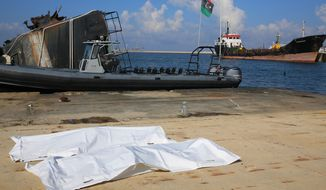 Bodies of two dead migrants lie on a dock after a rescue operation of more than 100 people by the Libyan Coast Guard near Tripoli, Libya, Monday, Dec. 21, 2015. (AP Photo/Mohamed Ben Khalifa) ** FILE **