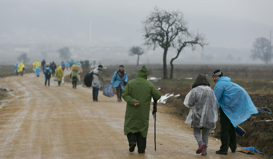 Migrants try to keep dry as they walk from the Macedonian border into Serbia, near the village of Miratovac, Serbia, Wednesday, Jan. 6, 2016. Hundreds of migrants continue to arrive daily into Serbia in order to register and continue their journey further north towards Western Europe. (AP Photo/Visar Kryeziu)