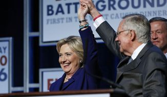 Senate Minority Leader Harry Reid, D-Nev., holds up the hand of Democratic presidential candidate Hillary Clinton on stage at the Battle Born Battleground First in the West Caucus Dinner, Wednesday, Jan. 6, 2016, in Las Vegas. Democratic presidential candidate, former Maryland Gov. Martin O'Malley is at right. (AP Photo/John Locher) ** FILE **