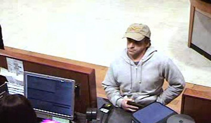 "A surveillance photo provided by the Medford, Ore., Police Department shows a bank robber who demanded cash from a Chase Bank branch in Medford, Ore., on Monday, Jan. 4, 2016. The Mail Tribune reports that Medford police shared surveillance photos of the bank robbery suspect on social media, leading many people to comment that the photo looked a lot like ""Dirty Jobs"" television host Mike Rowe. Police are still looking for the real suspect.  (Medford Police Department via AP)"