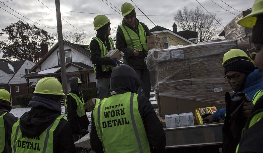 The Genesee County Sheriff's office and a work detail of people sentenced to community service hand out water filters and gallons of water to residents of Flint's north side on Thursday, Jan. 7, 2016, in Mich. Michigan's governor pledged additional state assistance Thursday for the southeastern Michigan city of Flint as it deals with elevated lead levels in its drinking water, but he provided little detail about what additional help and money would be provided.  (Sean Proctor /The Flint Journal-MLive.com via AP) LOCAL TELEVISION OUT; LOCAL INTERNET OUT; MANDATORY CREDIT