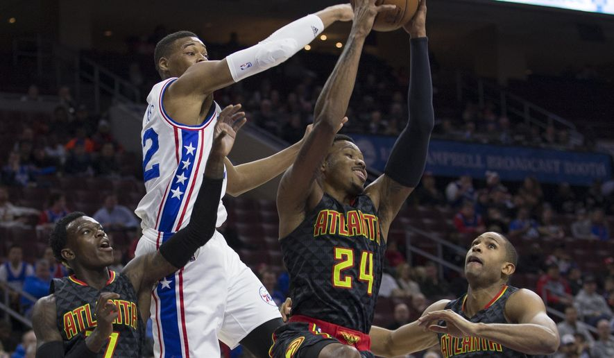 Atlanta Hawks' Kent Bazemore, center right, pulls down the rebound with Philadelphia 76ers' Richaun Holmes, center left, reaching from behind as Hawks' Dennis Schroder, left, and Al Horford, right, watch during the first half of an NBA basketball game Thursday, Jan. 7, 2016, in Philadelphia. (AP Photo/Chris Szagola)
