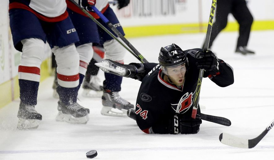 In this photo taken Thursday, Dec. 31, 2015,  Carolina Hurricanes' Jaccob Slavin falls to the ice while chasing the puck during an NHL hockey game against the Washington Capitals in Raleigh, N.C. Since the Hurricanes reconstituted their defense with six United States-born skaters, the Hurricanes have been a tougher team to beat. (AP Photo/Gerry Broome)