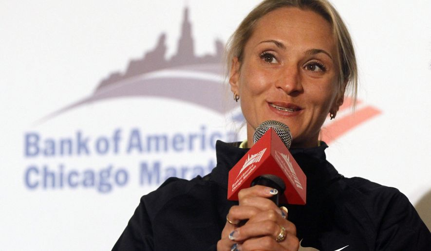 FILE - In this Friday, Oct. 5, 2012 file photo, Liliya Shobukhova from Russia responds to a question during a news conference of elite runners participating in the Chicago Marathon, in Chicago. The son of former IAAF president Lamine Diack and two Russian officials were banned from track and field for life on Thursday, Jan. 7, 2015 for engaging in blackmail, bribery and extortion to cover up a Russian doping case. The sanctions centered on the case of Russian marathoner Liliya Shobukhova, who was allegedly extorted out of hundreds of thousands of dollars to avoid a doping ban before the 2012 London Olympics. (AP Photo/Charles Rex Arbogast, file)