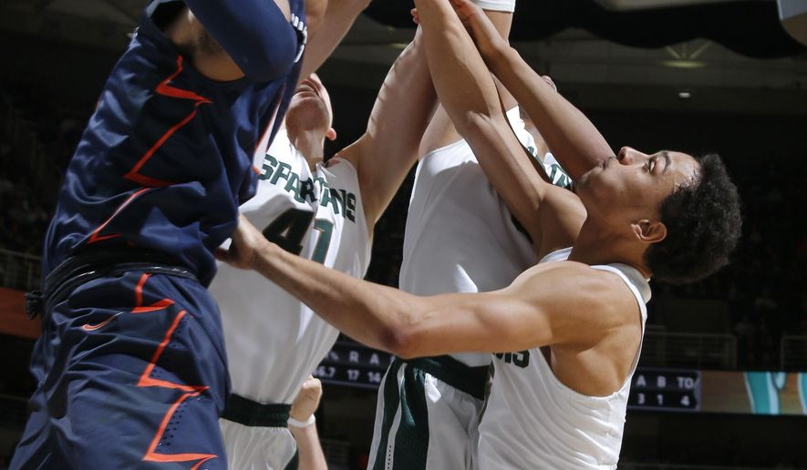 Illinois' D.J. Williams, left, and Michigan State's Colby Wollenman (41), Alvin Ellis III and Bryn Forbes, right, compete for a rebound during the first half of an NCAA college basketball game, Thursday, Jan. 7, 2016, in East Lansing, Mich. (AP Photo/Al Goldis)
