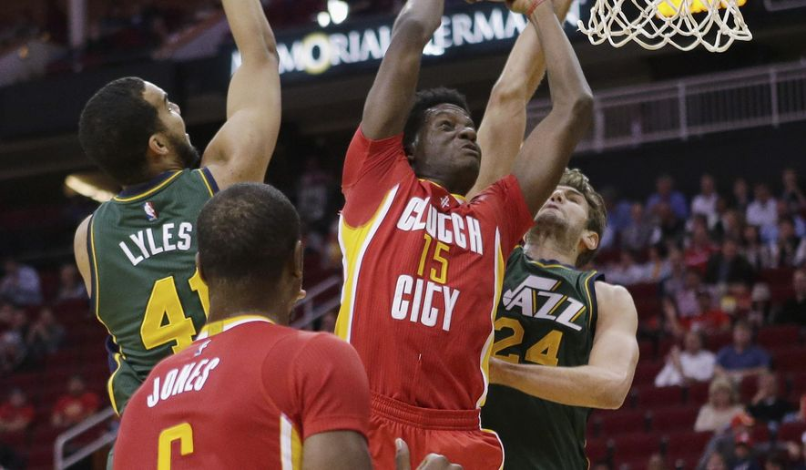 Houston Rockets forward Clint Capela (15) drives to the basket past Utah Jazz forward Trey Lyles (41) and center Jeff Withey (24) as Rockets forward Terrence Jones (6) looks on during the first half of an NBA basketball game Thursday, Jan. 7, 2016, in Houston. (AP Photo/Bob Levey)