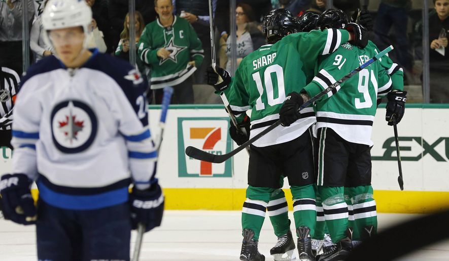 Dallas Stars' Patrick Sharp (10) and Tyler Seguin (91) celebrate Seguin's goal against the Winnipeg Jets during the first period of an NHL hockey game, Thursday, Jan. 7, 2016, in Dallas. (AP Photo/Mike Stone)
