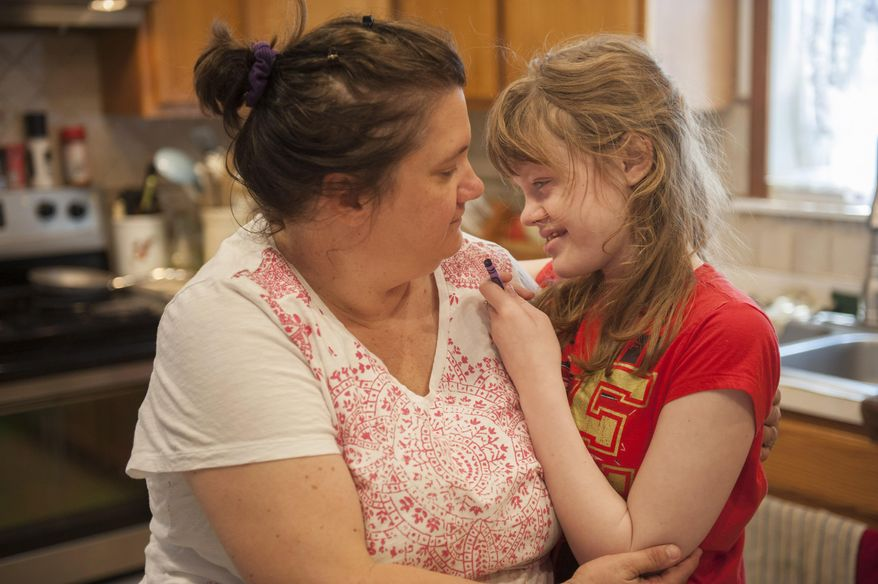 In this June 10, 2015 photo, medical marijuana patient Genny Barbour, who is autistic and suffers from seizures, interacts with her mother Lora at their home in Maple Shade, N.J. (John Ziomek/Camden Courier-Post via AP)  NO SALES; MANDATORY CREDIT