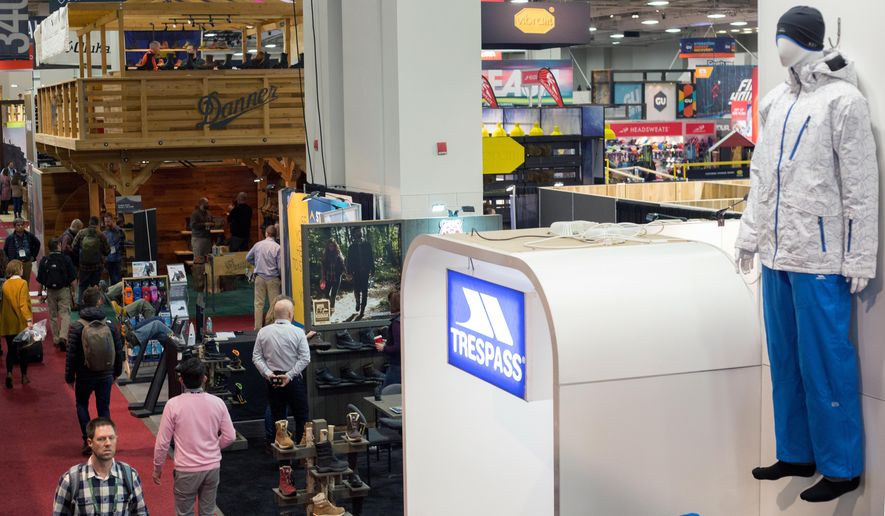 Attendees walk past displays for retail companies at the Outdoor Retailer Show on Thursday, Jan. 7, 2016, in Salt Lake City.  Show organizers announced in August that the expo will stay in Utah through 2018, expressing confidence Utah can remain the long-term home. The expo is staged twice a year and brings the state an estimated $45 million annual economic impact. (AP Photo/Kim Raff)