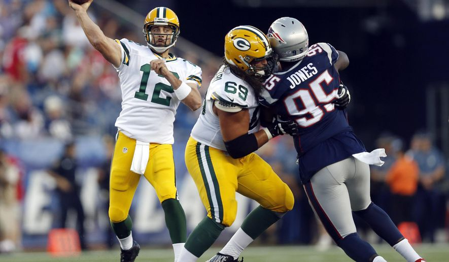 FILE - In this Aug. 13, 2015, file photo, Green Bay Packers quarterback Aaron Rodgers (12) passes as tackle David Bakhtiari (69) blocks New England Patriots defensive end Chandler Jones (95) during an NFL preseason football game in Foxborough, Mass. There appears to be growing optimism with the Green Bay Packers that injured left tackle David Bakhtiari could be ready for Sunday's wild-card playoff game against the Washington Redskins. (AP Photo/Michael Dwyer, File)