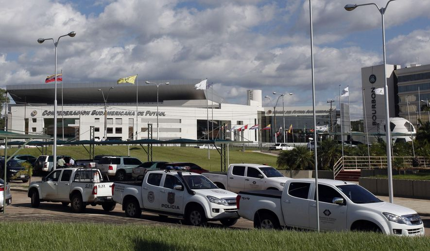 Police vehicles are parked outside the headquarters of the South American soccer confederation known as CONMEBOL in Asuncion, Paraguay,  Thursday, Jan. 7, 2016. Paraguayan authorities raided the CONMEBOL headquarters Thursday in connection to the sprawling FIFA probe being led by U.S. and Swiss prosecutors. (AP Photo/Cesar Olmedo)