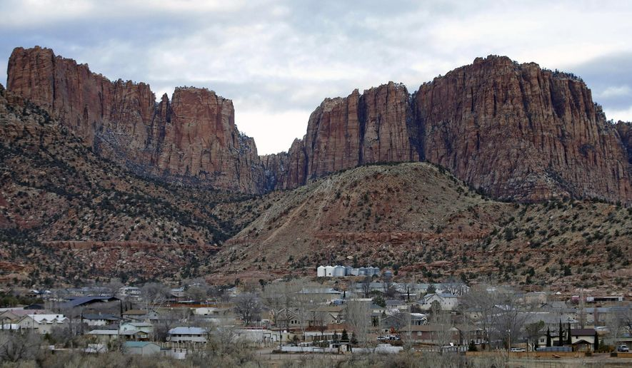 This Dec. 16, 2014, file photo shows Hildale, Utah, sitting at the base of Red Rock Cliff mountains, with its sister city, Colorado City, Ariz., in the foreground. A trial that begins January 2016 in Phoenix is expected to reveal the inner workings of two secluded towns on the Arizona-Utah line that authorities say were acting as agents of a corrupt polygamist regime. (AP Photo/Rick Bowmer/ File)