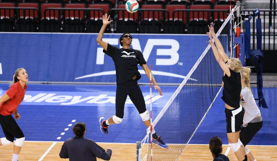U.S. middle blocker Foluke Akinradewo, center, prepares to spike the ball during team practice in Lincoln, Neb., Wednesday, Jan. 6, 2016. The U.S. plays Canada on Thursday in the NORCECA round-robin Olympic qualifying tournament in Lincoln. (AP Photo/Nati Harnik)