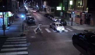 In this frame from a Thursday, Jan. 7, 2016 video provided by the Philadelphia Police Department, Edward Archer runs with a gun toward a police car driven by Officer Jesse Hartnett in Philadelphia. Archer, using a gun stolen from police, said he was acting in the name of Islam when he ambushed Hartnett sitting in his marked cruiser at an intersection, firing shots at point-blank range, authorities said. (Philadelphia Police Department via AP)