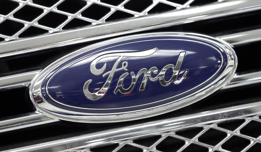 The Ford logo shines on the front grille of a 2014 Ford F-150, on display at a local dealership in Hialeah, Fla., int his Jan. 5, 2015, file photo. (AP Photo/Alan Diaz, File)