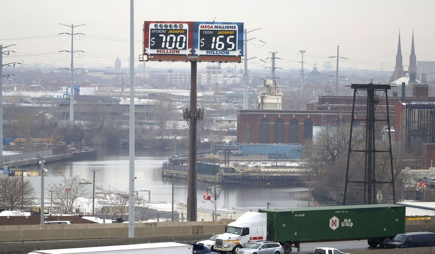 Motorists traveling on the interstate highway near downtown Chicago pass by an electronic billboard of the current jackpots for the Powerball and Mega-Millions lotteries, Thursday, Jan. 7, 2016, in Chicago. (AP Photo/Charles Rex Arbogast)