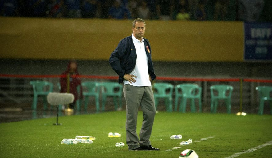 In this Aug. 9, 2015 photo, China's coach Alain Perrin stands in the rain on the sidelines during his team's East Asian Cup soccer match against Japan in Wuhan in central China's Hubei Province. The Chinese National Football Association said Friday, Jan. 8, 2016, that Perrin was departing following discussions between the sides and the search for a replacement would begin immediately. (AP Photo/Mark Schiefelbein)