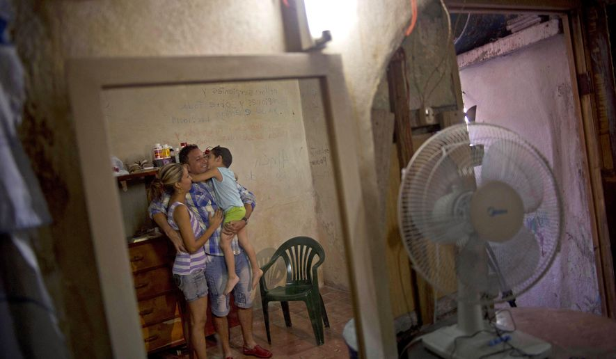 FILE - In this Jan. 9, 2015 file photo, dissident Wilberto Parada is reflected in a mirror with his wife and son during an interview, one day after his release from jail, at his home in Havana, Cuba. Cuban officials did not respond to requests for comment on how freed dissidents are faring. Among those back behind bars is Parada, who was arrested for public disorder in October 2015 when he protested in front of a prosecutor's office in Havana. (AP Photo/Ramon Espinosa, File)
