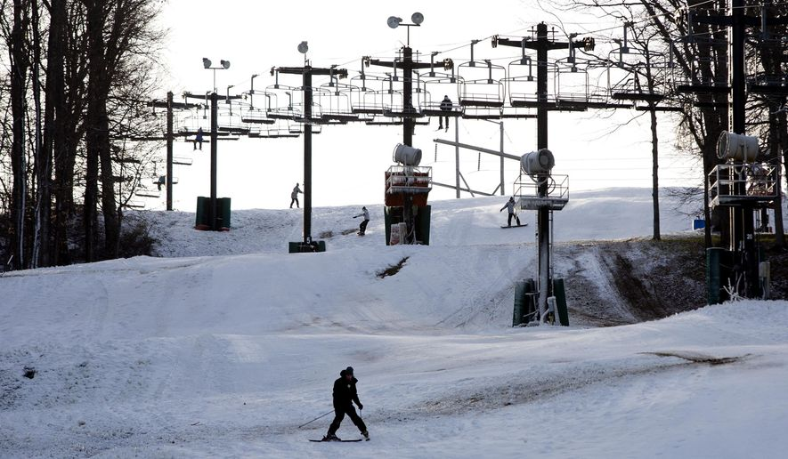 In this photo taken Tuesday, Jan. 5, 2016, skiers and snowboarders ride down a hill at Paoli Peaks in Paoli, Ind. Paoli Peaks opened on Jan. 4 with limited terrain because of December's unseasonably warm temperatures. (Ariana van den Akker/The Herald via AP) MANDATORY CREDIT