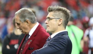 FILE - In this Dec. 27, 2015,  file photo, Atlanta Falcons General Manager Thomas Dimitroff, right, stands next to Falcons owner Arthur Blank before the first half of an NFL football game against the Carolina Panthers in Atlanta. Blank says he is sticking with general manager Thomas Dimitroff, who he says has formed a productive management team with first-year coach Dan Quinn. Blank said Friday there will be changes in the pro personnel and scouting departments. (AP Photo/John Bazemore, File)