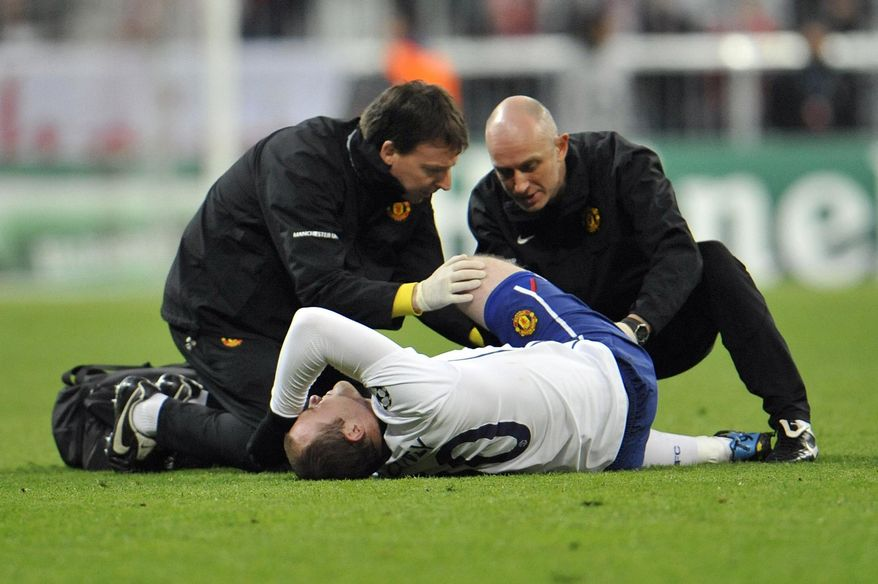 FILE - This is a Tuesday, March 30, 2010 file photo of Manchester's Wayne Rooney receiving medical treatment after getting injured during the Champions League quarterfinal first leg soccer match  between FC Bayern Munich and Manchester United in Munich, southern Germany. Soccer's rule-makers have overhauled the globally-applicable laws of the game in an attempt to remove inconsistencies and make them more user-friendly. If a player is injured from a challenge which is punished by a red or yellow card he can have quick treatment on the field of play and does not have to leave. It always seemed unfair that the victim team was down to 10 men and the guilty team has 11 against 10. (AP Photo/Kerstin Joensson, File)