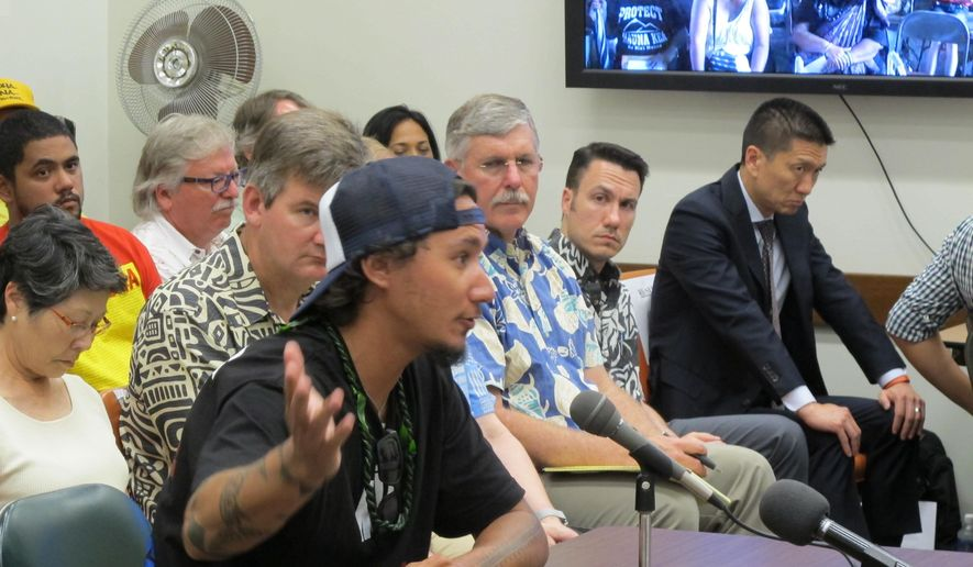 File-This July 10, 2015, file photo shows protest leader Kahookahi Kanuha, foreground, testifying  before a Board of Land and Natural Resources meeting in Honolulu  against a state proposal to limit the ability of protesters to access Mauna Kea.  Kanuha was arrested while blocking telescope construction crews on a Hawaii mountain has been found not guilty after a trial where he testified in Hawaiian. Kanuha's  case had been postponed because he insisted on defending himself in the language he's most comfortable speaking. The trial went forward Friday with a Hawaiian interpreter. Judge Barbara Takase found him not guilty of obstructing. (AP Photo/Jennifer Sinco Kelleher, File)