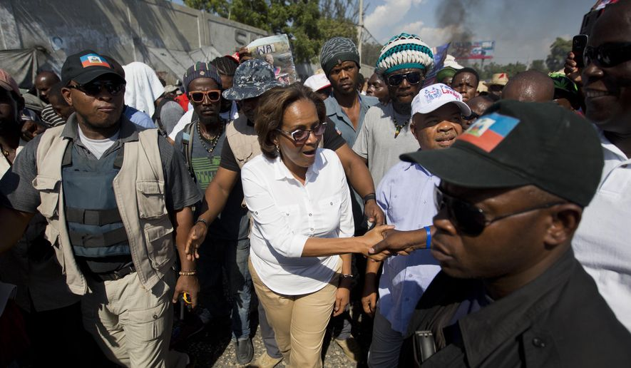 Presidential candidate Maryse Narcisse, center, greets supporters during a protest against the government in Port-au-Prince, Haiti, Friday, Jan. 8, 2016. Campaigning for Haiti's presidential runoff has kicked off, but it appears there's only one candidate actively participating. Government-backed contender Jovenel Moise was scheduled to hold his first runoff rally late Friday. But No. 2 candidate Jude Celestin's team says he will only take part in the vote if sweeping changes are made to electoral machinery. (AP Photo/Dieu Nalio Chery)