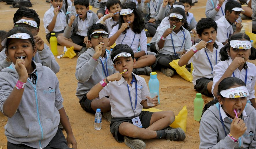 Indian school children brush their teeth in an attempt to make a record in Bangalore, India, Thursday, Jan. 7, 2016.Thousands of students from different schools gathered in a single venue and brushed their teeth in an attempt to enter into the Guinness Book of World Records. (AP Photo/Aijaz Rahi)