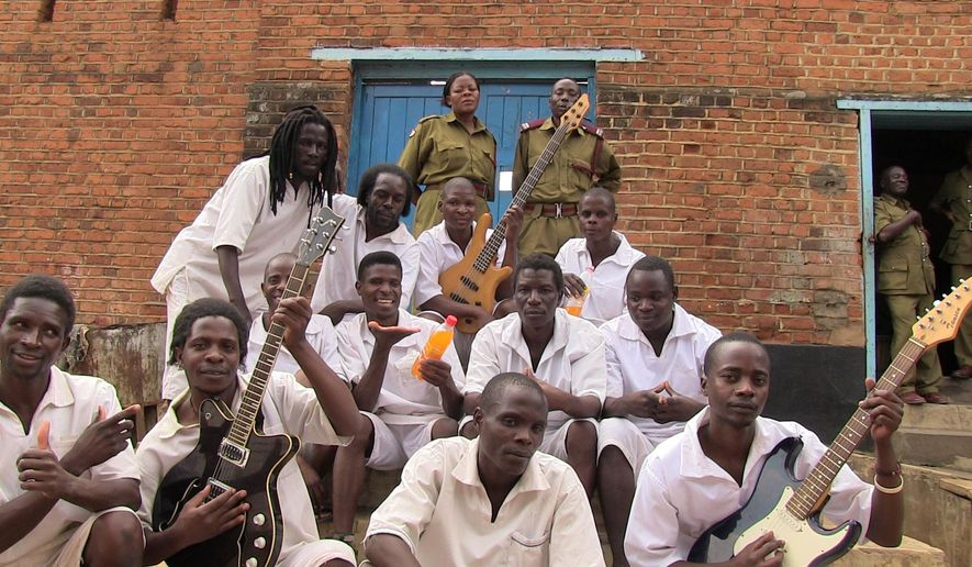 In this photo taken August 23, 2014 and supplied by the Zomba Prison Project, members of the Zomba Prison group pose for a photograph with prison gurads at the Zomba Prison, in southern Malawi. The gentle chorus of maximum security prisoners singing over guitar chords has earned Malawi its first Grammy nomination making history in the impoverished African nation. (Marilena Delli/Zomba Prison Project via AP)