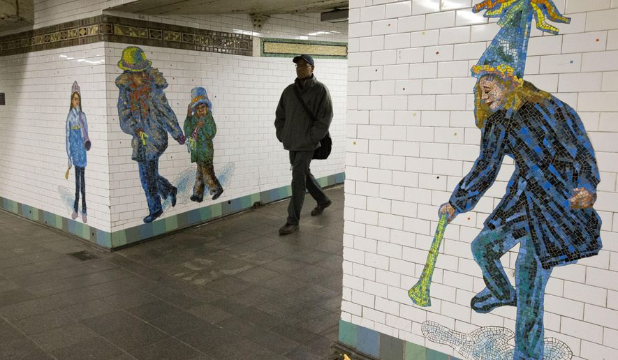 A commuter walks past mosaics adorning the walls of the Times Square subway station, Thursday, Jan. 7, 2016, in New York. (AP Photo/Mary Altaffer)