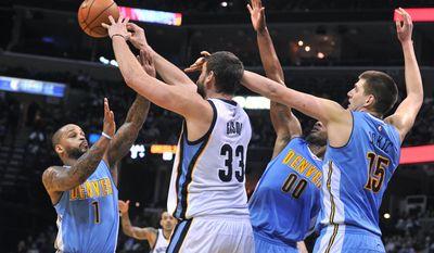 Memphis Grizzlies center Marc Gasol (33) passes among defense by Denver Nuggets guard Jameer Nelson (1), forward Darrell Arthur (00), and center Nikola Jokic (15) during the second half of an NBA basketball game Friday, Jan. 8, 2016, in Memphis, Tenn. (AP Photo/Brandon Dill)
