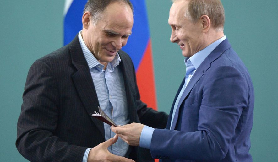 Russian President Vladimir Putin, right, congratulates Russian national coach of judo Italy's Ezio Gamba while granting him a Russian passport in the resort city of Sochi, Russia, Friday, Jan. 8, 2016. After Russian President Vladimir Putin and national judo team coach Ezio Gamba took each other to the mat in a practice, Putin followed up with a smooth move, granting the Italian a Russian passport. (Alexei Nikolsky, Sputnik, Kremlin Pool Photo via AP)