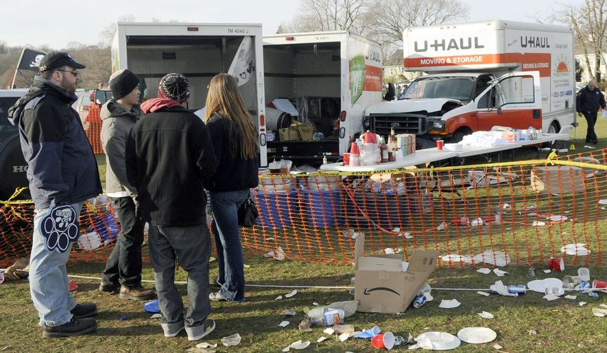 FILE --In this Nov. 19, 2011 file photo, people look at the scene of a fatal accident in a parking area outside an NCAA college football game between Harvard and Yale in New Haven, Conn. The U-Haul truck carrying beer kegs, heading to the Sigma Phi Epsilon tailgating area outside the Yale Bowl, fatally struck 30-year-old Nancy Barry, of Salem, Mass., and injured two other women. A lawyer for the Barry family said Friday, Jan. 8, 2016, that the family, the Yale University fraternity and more than 80 of its members have settled lawsuits over the fatal wreck. (AP Photo/Bob Child, File)