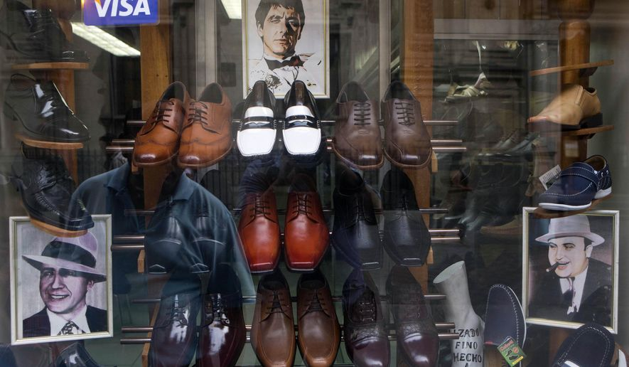 FILE - This Thursday, Jan. 22, 2015 file photo shows portraits of actor Al Pacino as character Tony Montana, center, gangster Al Capone, right, and Latin American tango icon Carlos Gardel, left, in a display in a men's shoe store in downtown Lima, Peru. The store owner said he sells shoe styles that these famous men and character used. (AP Photo/Esteban Felix)