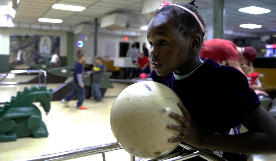 ADVANCE FOR THE WEEKEND OF JAN 9-10 AND THEREAFTER - In a Saturday, Dec. 19, 2015 photo, Nyaduop Grang, 5, bowls at Immaculate Conception Church's bowling alley in Omaha. The alley looks similar to when it opened in the 1950s and is usually used for birthday parties and family gatherings. (Sarah Hoffman/The World-Herald via AP) MAGS OUT TV OUT US ONLY