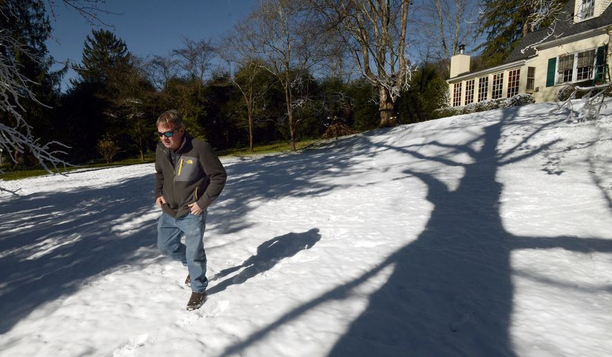 """In this Jan. 5, 2016 photo, Blair Bullock walks by his home after he used a homemade snow machine to cover his front yard with snow, in Bristol, Va. The snow, which began """"falling"""" Monday night and continued into Tuesday morning, is the manmade variety thanks to a snow gun — a combination of pipe, valves and an oscillating electric motor — engineered and built by Bullock. (David Crigger/The Bristol Herald-Courier via AP) MANDATORY CREDIT"""
