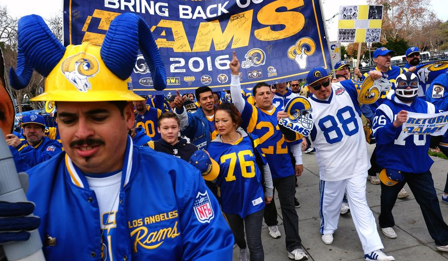 Rams football fans hold banners, wave signs and chant while marching around the historic Los Angeles Memorial Coliseum. Saturday, Jan. 9, 2016 in Los Angeles. Boisterous Los Angeles Rams fans gathered Saturday to herald the NFL football team's possibly imminent return to Southern California after a 21-year sojourn in St. Louis. (AP Photo/Richard Vogel)