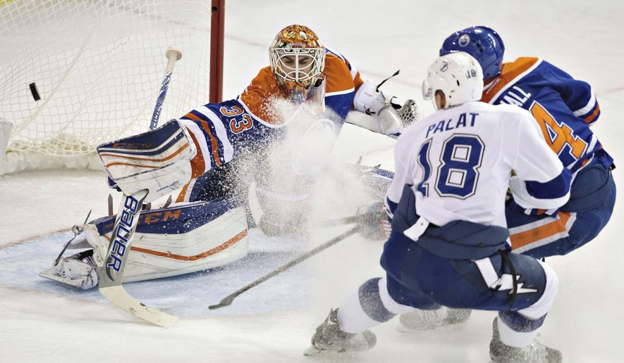Tampa Bay Lightning's Ondrej Palat (18) and Edmonton Oilers' Taylor Hall (4) watch the puck go past Oilers goalie Cam Talbot (33) during the third period of an NHL hockey game Friday, Jan. 8, 2016, in Edmonton, Alberta. (Jason Franson/The Canadian Press via AP)