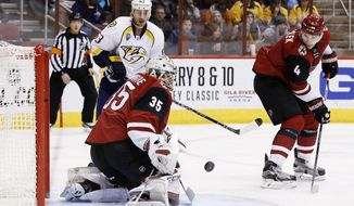 Arizona Coyotes' Louis Domingue (35) makes a save on a shot by Nashville Predators' Mike Ribeiro (63) as Coyotes' Zbynek Michalek (4), of the Czech Republic, watches the puck for a rebound during the first period of an NHL hockey game Saturday, Jan. 9, 2016, in Glendale, Ariz. (AP Photo/Ross D. Franklin)