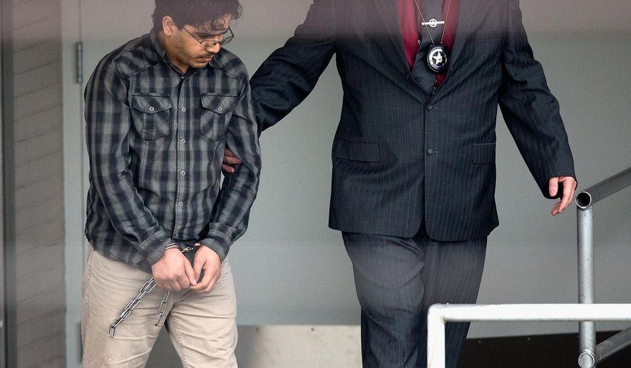 Omar Faraj Saeed Al Hardan, left, is escorted by U.S. Marshals from the Bob Casey Federal Courthouse on Friday, Jan. 8, 2016, in Houston. Al Hardan made his initial appearance in federal court in Houston Friday morning after he was indicted Wednesday on three charges related to accusations he tried to provide material support to the Islamic State group.  (AP Photo/Bob Levey)